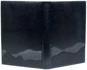 John Muir. Heaven on Earth. Illustrated by Charles D. Jones. Austin: Press Intermezzo, 1998. A French style binding with laced-on boards. The top edge is graphite with red silk hand sewn endbands. The book is covered in black goatskin with black emery paper and black morocco onlays, enclosed in a traditional chemise and slipcase. The shape and texture of the onlays suggest the mountain ranges dear to John Muir in his exploration of Yosemite. Sample binding submitted to the 2009 DeGolyer competition